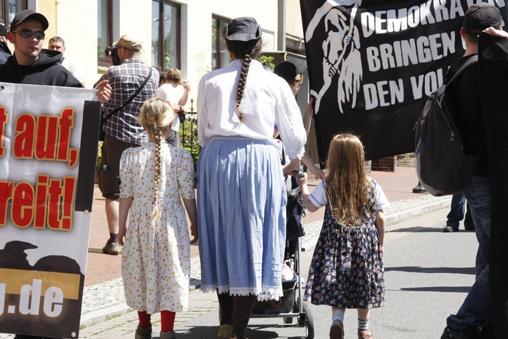 """Frau mit Töchtern im typisch """"völkischen"""" Kleidungsstil"""""""